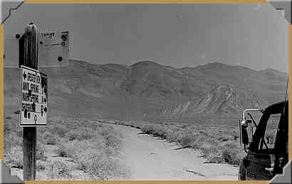 Road sign and Striped Butte - 10/1976.